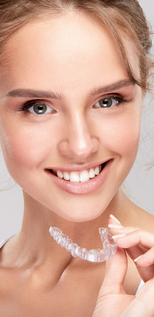 Smiling young girl holding invisalign