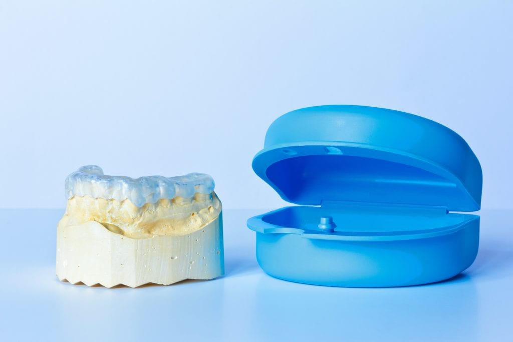 Dental mouthguard on a tooth model next to a blue plastic case