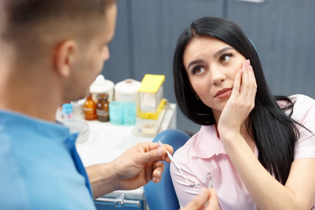 Woman talking to dentist while holding her cheek