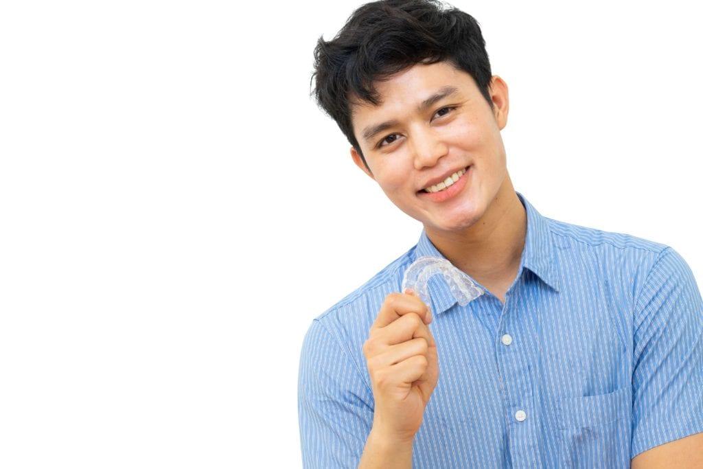 Teenage boy holding Invisalign aligner