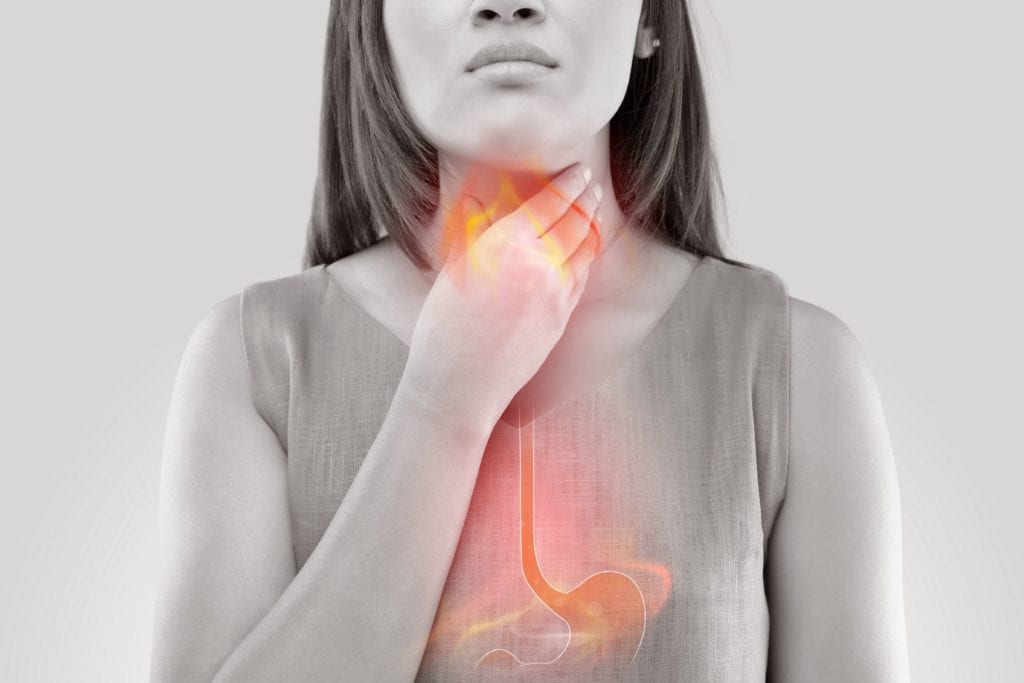woman holding her throat and suffering from acid reflux